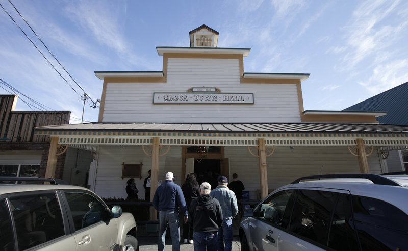 Voters arrive at the Genoa Town Hall for a Nevada Republican caucus meeting Saturday in Genoa, Nev. The economy still figures to be the chief issue in the presidential campaign.