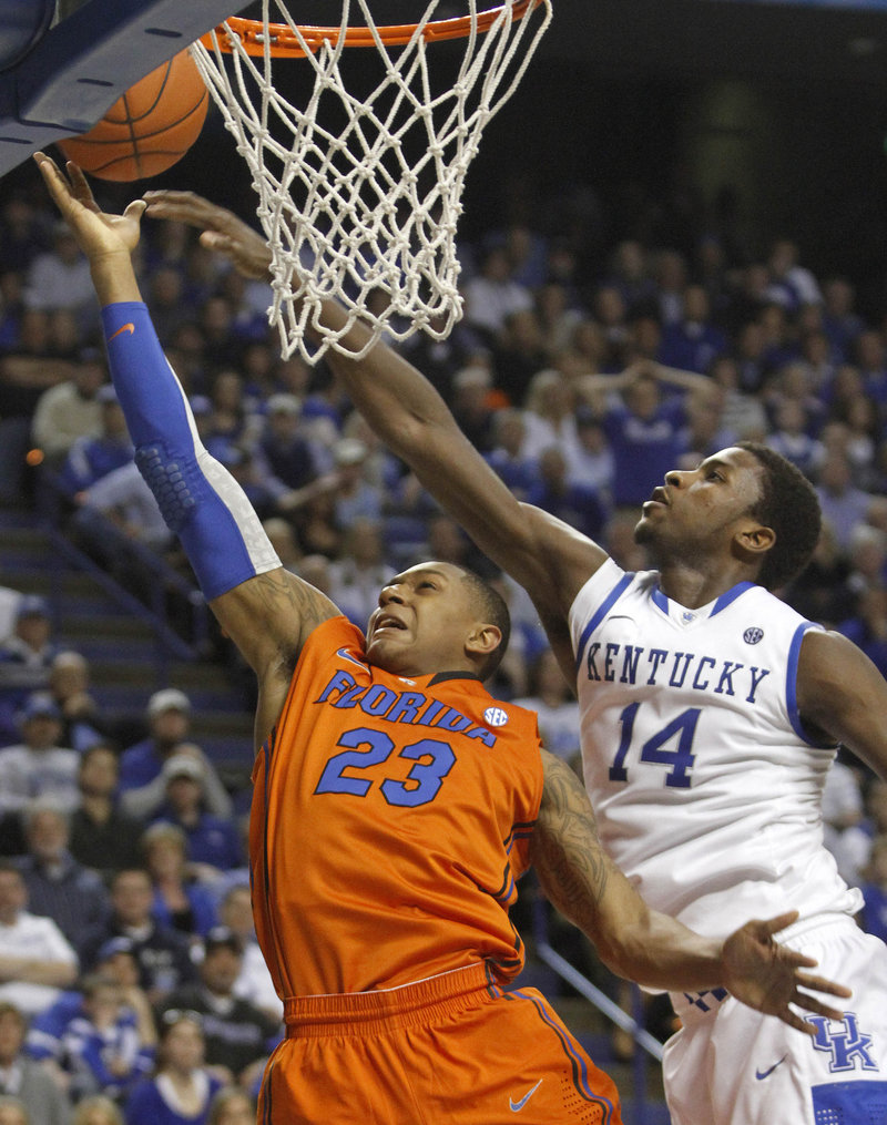 Bradley Beal of Florida is pressured by Kentucky's Michael Kidd-Gilchrist in Tuesday night's game at Lexington, Ky. Top-ranked Kentucky won, 78-58.