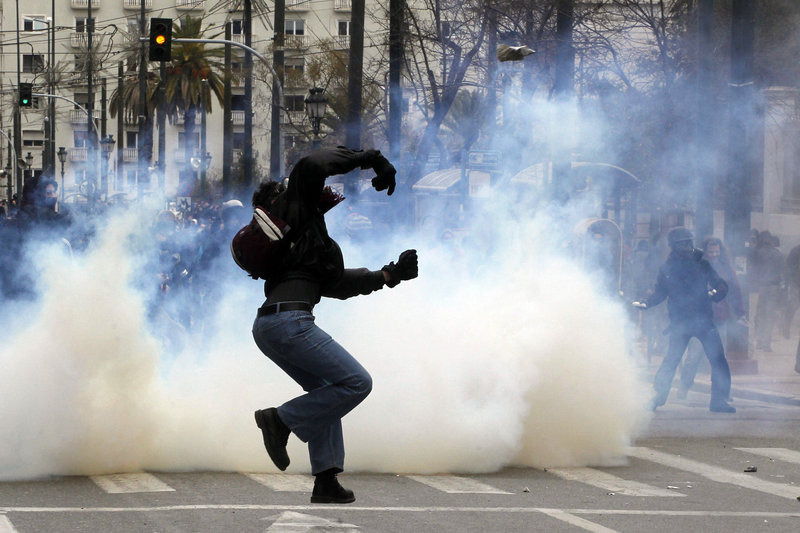 A protester throws a stone toward riot police in Athens on Friday as a cloud of tear gas envelops another at an anti-austerity demonstration.