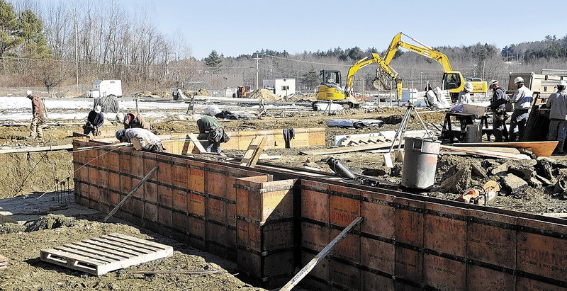 Workers build the foundation for the new Kennebec Ice Arena on Friday in Hallowell. It will replace the old arena, the roof of which collapsed last winter under a load of snow.