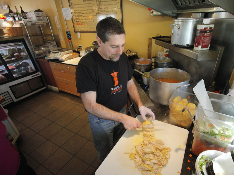 Pete Leavitt of Leavitt & Sons Deli in Falmouth shreds chicken for some of the 15 to 30 pies he sells daily.