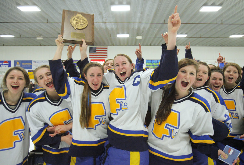 Falmouth captains Megan Fortier, third from left, and Monica Aaskov lift the trophy Wednesday night after the Yachtsmen won the West championship in girls' hockey with a 4-0 victory against York. Falmouth will meet Greely for the state championship Saturday night.