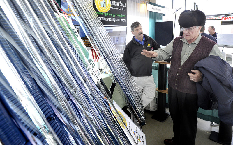 Earl Allen, right, of Scarborough talks with Ted Hellier about solar panel installation Saturday at the Maine Home, Remodeling and Garden Show at the Cumberland County Civic Center.