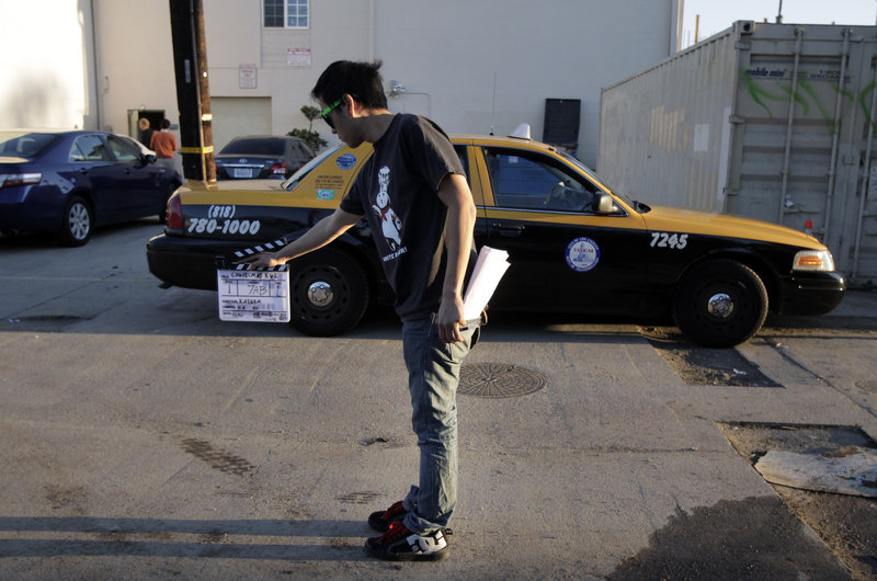 Crew member Arthur Hong holds a clapboard while filming holiday movie trailers at Maker Studios in Culver City, Calif. The $100 million investment by YouTube in 96 new channels starting in October has sparked a flurry of activity in Hollywood's independent producer community.
