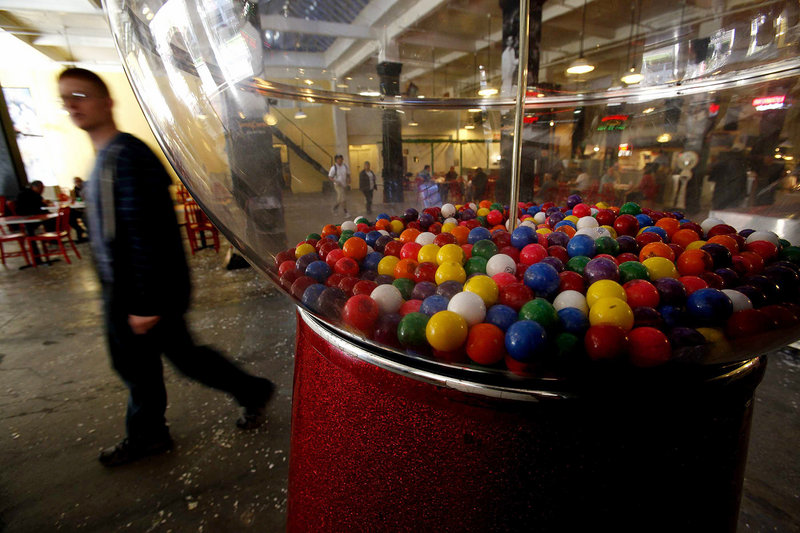 A giant gum ball machine stands in the back of Grand Central Market in Los Angeles. As sales of gum balls have declined, many of the old-time machines dispense toys.