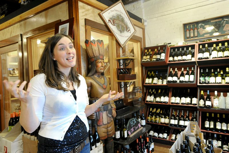 """Erin Hadwen, manager and """"wine goddess"""" at the Old Port Wine Merchants and Cigar Shoppe, says the store has gained business since it moved from Fore Street to Commercial Street in 2009. Hadwen says the tourist traffic is better and that local customers say they are more aware of it now."""