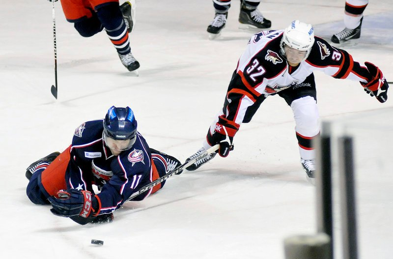 Adam Mair of Springfield dives for a loose puck and lands on Ryan Duncan's stick during Sunday's game at the Cumberland County Civic Center. The Falcons beat the Pirates, 6-2. Springfield has won 5 of seven against the Pirates.