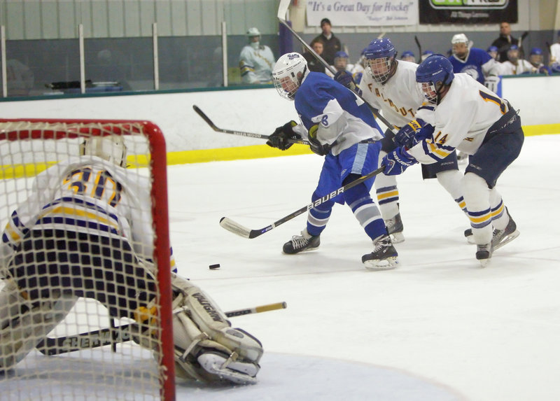 Jack Kennedy of Kennebunk tries to put a shot on Falmouth goalie Dane Pauls while being challenged by Ben Freeman, center, and Jack Pike. Falmouth advanced to the Western Class A semifinals by pulling away to a 10-1 victory Tuesday night.