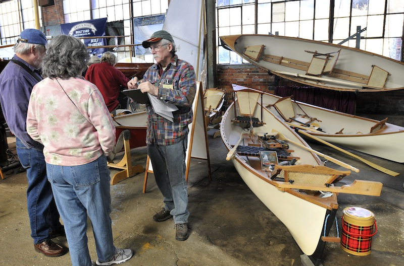 Steve Kaulback, founder of Adirondack Guideboat Inc., out of Charlotte, Vt., talks with visitors during The Maine Boatbuilders Show at the Portland Company Complex on Sunday, March 18, 2012.