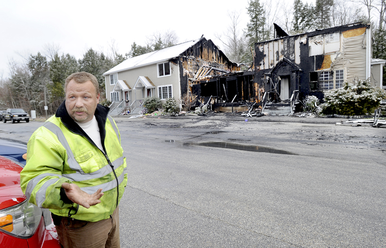 Casey Farley stands outside his gutted condo at 20 Calla Way in Windham after he awoke to flames outside his window and alerted his family and adjacent neighbors to safety.