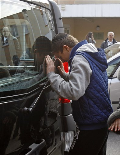A youngster cries against a hearse today, following a ceremony at the Ozar Hatorah Jewish school in Toulouse, where a gunman opened fire on Monday, killing four people.