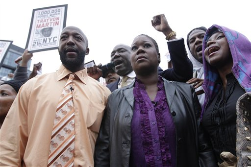 Trayvon Martin's parents, Tracy Martin, left, and Sybrina Fulton, center, are joined by an unidentified woman during the Million Hoodie March in Union Square Wednesday in New York.