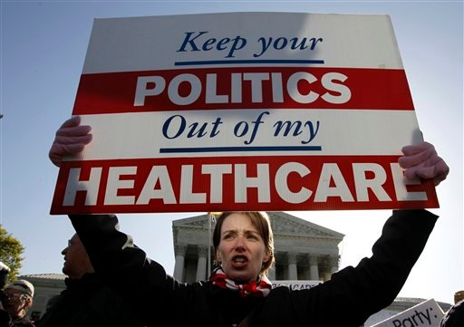 Amy Brighton from Medina, Ohio, who opposes health care reform, rallies in front of the Supreme Court in Washington on Tuesday. The court continues arguments today on the health care law signed by President Barack Obama.