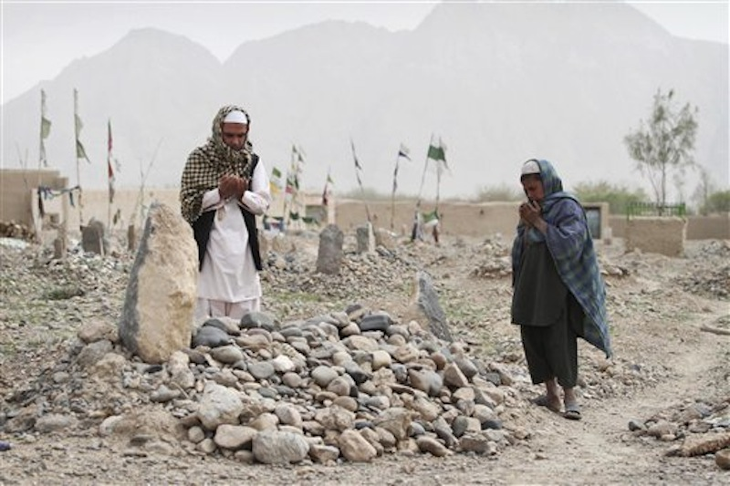 Afghan villagers pray over the grave of one of the sixteen victims killed in a shooting rampage in the Panjwai district of Kandahar province south of Kabul, Afghanistan on Saturday, March 24, 2012. Mohammad Wazir has trouble even drinking water now, because it reminds him of the last time he saw his seven-year-old daughter. He had asked his wife for a drink but his daughter insisted on fetching it. Now his daughter Masooma is dead, killed along with 10 other members of his family in a shooting rampage attributed to a U.S. soldier. The soldier faces the death penalty but Wazir and his neighbors say they feel irreparably broken. (AP Photo/Allauddin Khan)