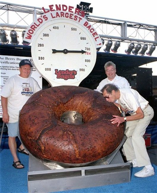 In this July 24, 1998 photo, Murray Lender kisses the world's largest bagel while baker Larry Wilkerson, left, and Lender's Bagel Bakery manager Jim Cudahy watch after the weight of the bagel was revealed during Bagelfest in Mattoon, Ill. Murray Lender, who helped turn his father's small Connecticut bakery into a national company that introduced bagels to many Americans for the first time, has died in Florida. He was 81. (AP Photo/Journal Gazette, Doug Lawhead)
