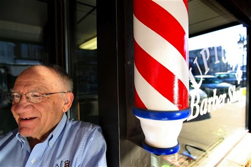 In this March 5, 2010 photo Howard Rettenmeier, who has cut hair for 55 years at the Uptown Barber Shop, stands by the barber pole at his Dyersville, Iowa, shop. The barber pole, one of the oldest signs that can be seen on storefronts across America, is an increasing source of friction between barbers and beauticians over which businesses get to display the iconic striped poles. (AP Photo/The Telegraph Herald, Dave Kettering)