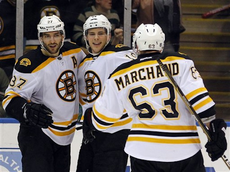 Boston Bruins' Patrice Bergeron (37) and Tyler Seguin (19) celebrate a goal by Bergeron as teammate Brad Marchand skates over during the third period of an NHL hockey game against the New York Islanders at the Nassau Coliseum in Uniondale, N.Y. on Saturday, March 31, 2012. Marchand and Seguin received assists on the goal in the Bruins' 6-3 win. (AP Photo/Paul J. Bereswill) Bruins Islanders Hockey