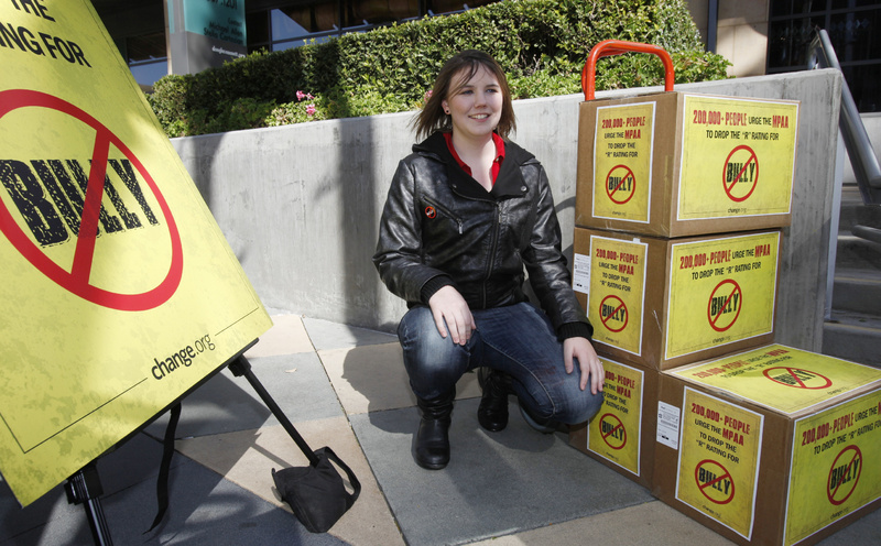"Katy Butler, 17, a high school student from Ann Arbor, Mich., poses by the petitions she delivered to the Motion Picture Association of America in Los Angeles on Wednesday. Butler is urging the MPAA to change the ""R"" rating to a ""PG"" for the ""Bully"" film."