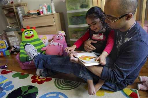Christopher Astacio reads with his daughter Cristina, 2, who was recently diagnosed with a mild form of autism.