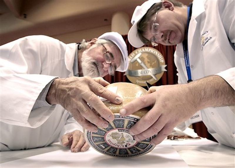 Russell Smith of Australia, left, and John Jaeggi of Madison prepare to sample one of the entries in the Smear Ripened Semi-soft Cheese category during the opening day of the World Championship Cheese Contest at the Monona Terrace Convention Center in Madison, Wis. on Monday, March 5, 2012. More than 2,500 entries will be judged throughout the three day gathering, sponsored every two years by the Wisconsin Cheese Makers Association. (AP Photo/Wisconsin State Journal, John Hart ) LOCAL;A3;CHEESE;WORLD CHAMPIONSHIP;DAIRY;JUDGE;MONONA TERRACE