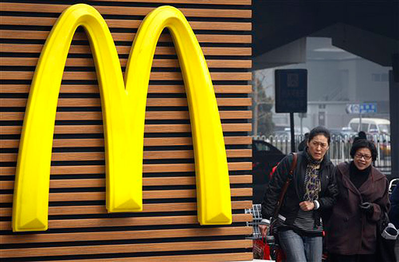 Chinese women walk past a McDonald's sign in Beijing on Friday, March 16, 2012. Chinese state television accused McDonald's and French retrailer Carrefour Thursday of selling expired chicken products in separate incidents amid public anxiety in China over food safety. (AP Photo/ Vincent Thian)