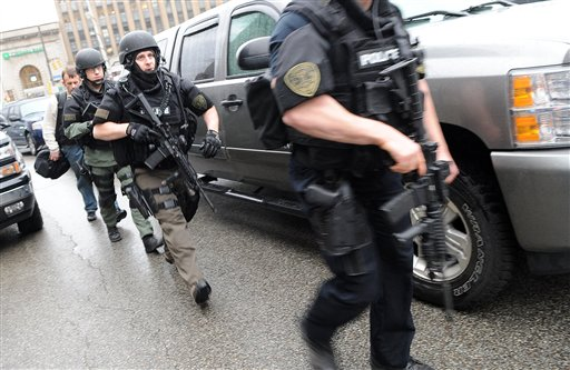 Police head up De Soto Street toward Western Psychiatric Institute and Clinic on Thursday in Pittsburgh, where a gunman opened fire, killing one person, and wounding several others.