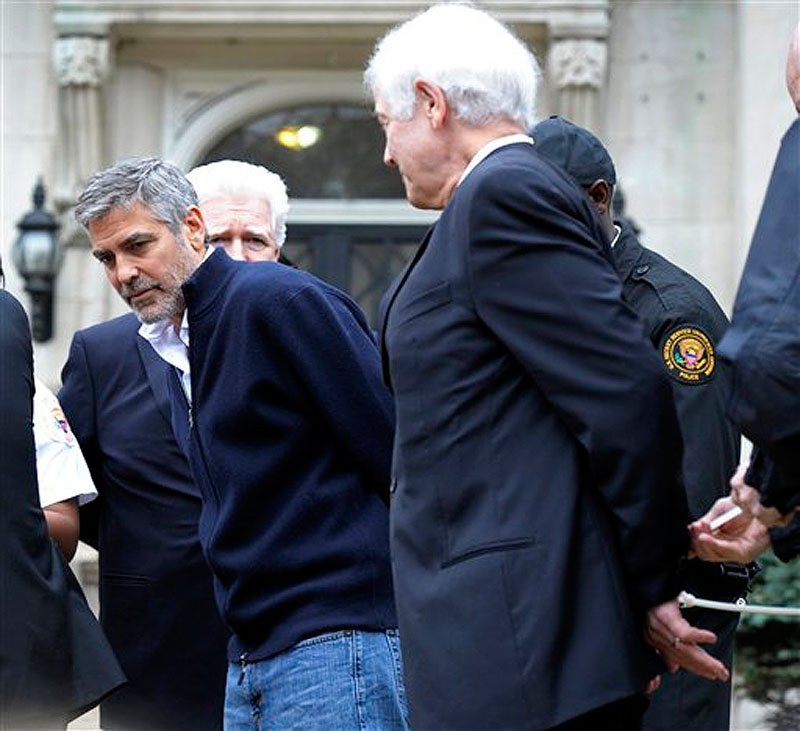 Actor George Clooney, center, Rep. Jim Moran, D-Va, back, and Clooney's father, Nick Clooney, right, are arrested during a protest at the Sudanese Embassy in Washington on Friday, March 16, 2012. The demonstrators are protesting the escalating humanitarian emergency in Sudan that threatens the lives of 500,000 people. (AP Photo/Cliff Owen)