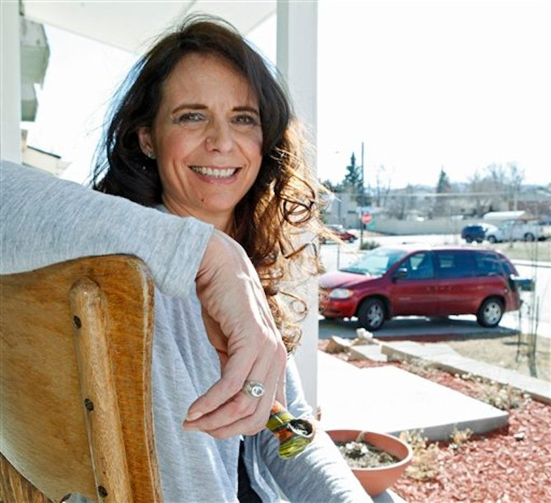 In this photo taken on Tuesday, March 6, 2012, Angeline Chilton a suburban Denver woman with multiple sclerosis who smokes pot twice a day to ease tremors, holds her pipe as she sits on the front porch of her home in Lakewood, Colo. States are struggling to come up with a blood-level standard for marijuana that would be analogous to the blood-alcohol standard used to decide who's driving drunk. (AP Photo/Ed Andrieski)
