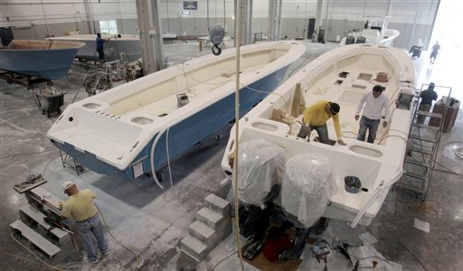 In this Jan. 11, 2012, photo, boat builders work on SeaHunter hulls at SeaHunter Boats in Princeton, Fla.