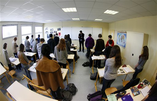 Unidentified pupils of the Anne-Franck college in Lambersart, northern France, and their class teacher Laurie Larvent, center, hold a minute of silence in their classroom today, the day after a gunman on a motorbike opened fire at a Jewish school in Toulouse, killing a rabbi and his two young sons as they waited for a bus, then chased down a 7-year-old girl, shooting her dead at point-blank range.