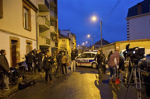 Journalists gather nearby as French police secure the area today where they exchanged fire and were negotiating with a gunman who claims connections to al-Qaida and is suspected of killing three Jewish schoolchildren, a rabbi and three paratroopers.