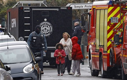 A woman and children are escorted by a police officer near a building where the chief suspect in an al-Qaida-linked killing spree is holed up in an apartment in Toulouse, France, today.