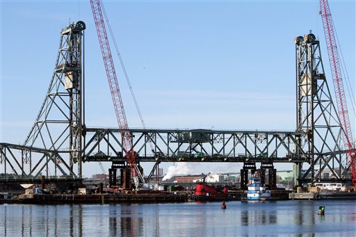 The 2 million pound lift span of the historic Memorial Bridge, connecting New Hampshire to Maine, is slowly dropped into a cradle on a barge, Wednesday, Feb. 8, 2012 in Portsmouth, N.H. The bridge is scheduled to be replaced by the summer of 2013. (AP Photo/Jim Cole)