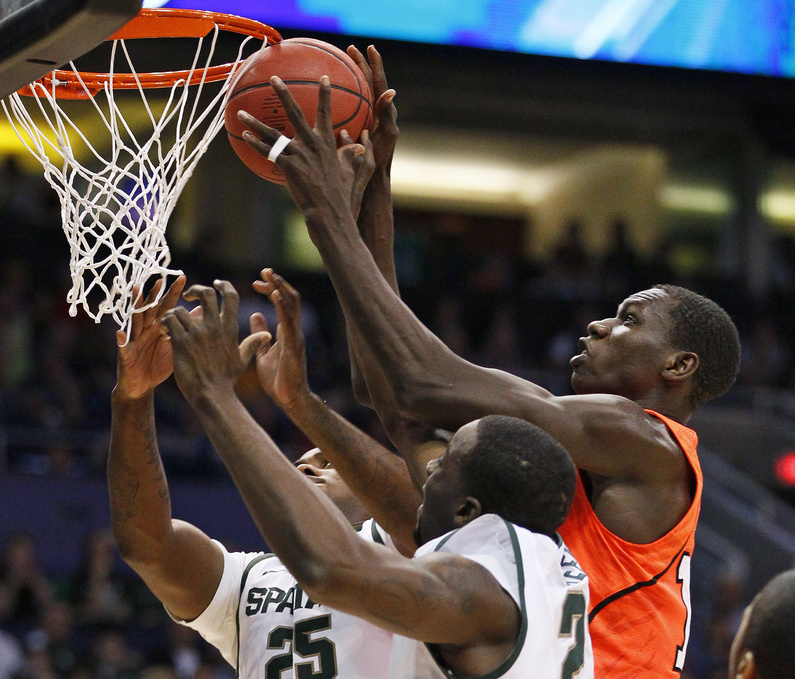 Michigan State's Derrick Nix, left, and Draymond Green, lower right, vie for possession of the ball with Louisville's Gorgui Dieng in the NCAA West Regional semifinal on Thursday.