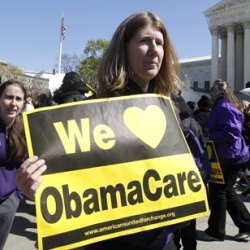 "Holding a sign saying ""We Love ObamaCare,"" supporters of health care reform rally in front of the Supreme Court on Tuesday."