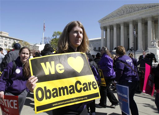 """Holding a sign saying """"We Love ObamaCare,"""" supporters of health care reform rally in front of the Supreme Court on Tuesday."""