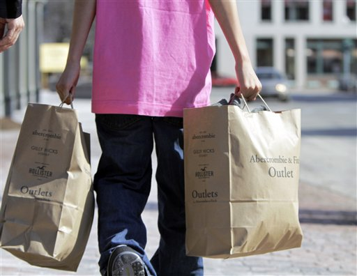 A shopper carries bags of merchandise in Freeport on Monday. February retail sales rose 1.1 percent, the biggest gain in five months, with autos showing strength.