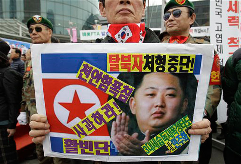 A South Korea's veteran holds a placard showing North Korea's new leader Kim Jong Un and flag during an anti-North Korea protest rally in Seoul, South Korea on Friday, March 16, 2012. North Korea announced Friday it will launch a long-range rocket mounted with a satellite in honor of late President Kim Il Sung's April birthday. (AP Photo/Lee Jin-man)