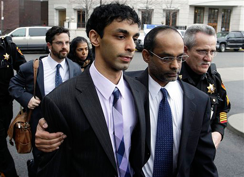 Dharun Ravi, center, is helped by his father, Ravi Pazhani, second right, as they leave court around in New Brunswick, N.J. on Friday, March 16, 2012. Defense attorney Philip Nettl follows, second left. Ravi, a former Rutgers University student accused of using a webcam to spy on his gay roommate's love life has been convicted of bias intimidation and invasion of privacy. A jury found that he used a webcam to spy on roommate Tyler Clementi. Within days, Clementi realized he had been watched and jumped to his death from New York's George Washington Bridge in September 2010. (AP Photo/Mel Evans)