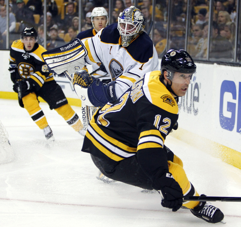 Brian Rolston (12) goes after the puck in front of Buffalo Sabres goalie Jhonas Enrothin (1) behind the net Thursday in Boston. The Bruins won, 3-1.