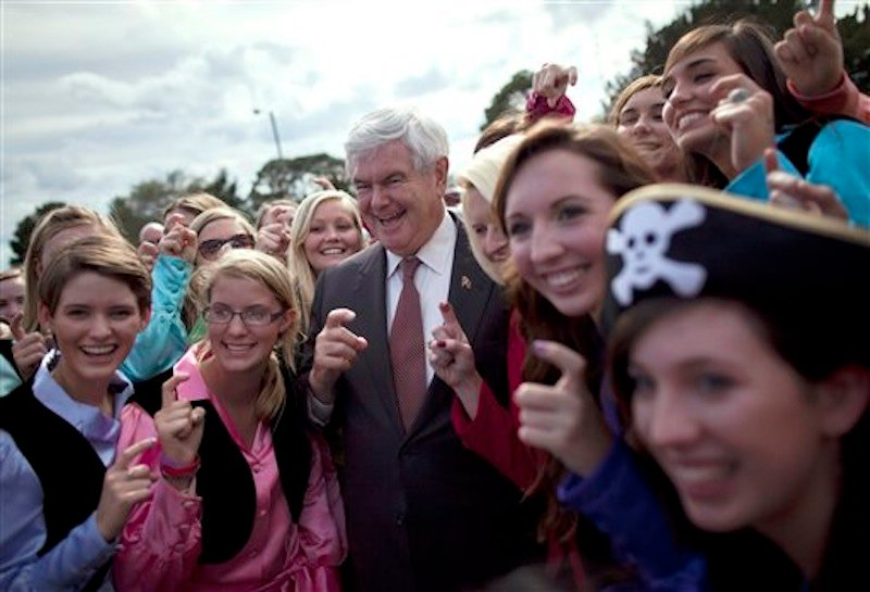 "Republican presidential candidate Newt Gingrich poses for photos with the ""Pirates of the Spanish Maine"" high school sorority before a rally, Friday, March 2, 2012, in Brunswick, Ga. (AP Photo/Evan Vucci)"