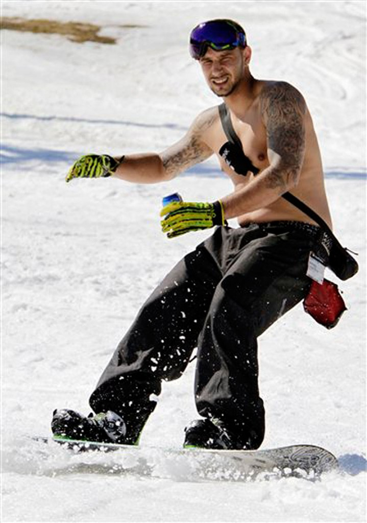 Jonathan DaRosa, of Taunton, MA., enjoys the warm sun while snowboarding in unusual weather for this time of year at Sunday River in Newry, Maine, on Wednesday, March 21, 2012. (AP Photo/Pat Wellenbach)
