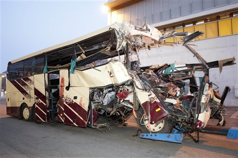 The wreckage of a tourist bus from Belgium is dragged by a tow truck outside the tunnel of the motorway A9, in Sierre, western Switzerland, early Wednesday, March 14, 2012. 28 people were killed in the bus crash. (AP Photo/Keystone, Laurent Gillieron)