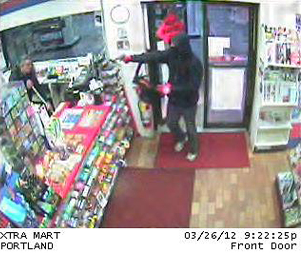 A surveillance camera captured this image of the XtraMart robbery in progress.