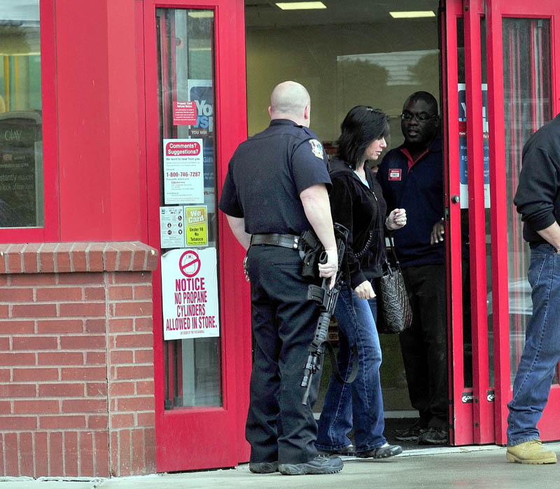 EXIT: Customers leave CVS Pharmacy on Kennedy Memorial Drive in Waterville past heavily armed police officer Denis Picard and a store employee while other officers search inside the store after a reported robbery on Sunday.