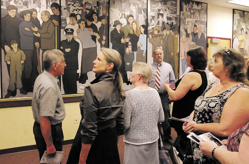 Interested Mainers study a mural by Judy Taylor depicting the history of labor in Maine. A judge ruled Friday that Gov. Paul LePage had a right to remove the mural. LePage's actions created a controversy in Maine.