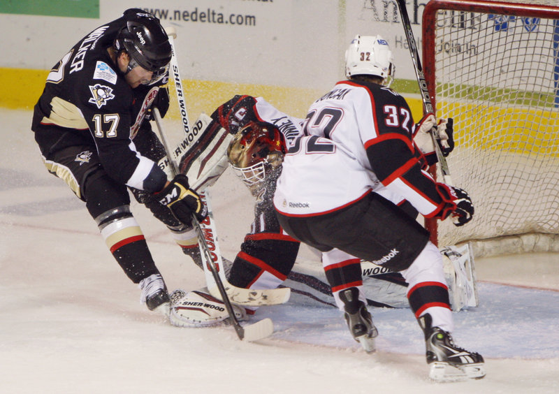 In this November 2011 photo, Portland goalie Curtis McElhinney clamps his glove on the, just beating the arrival of Geoff Walker of Wilkes-Barre/Scranton as Ryan Duncan of the Pirates moves in.