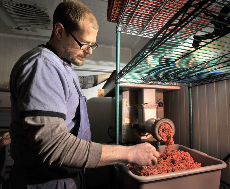 Butcher Jarrod Spangler grinds a batch of ground beef in the walk-in cooler at Rosemont Market's Brighton Avenue store in Portland recently. Spangler, who trained in Italy, hand-butchers locally raised, mostly organic, pasture-raised animals. Buying local attracts customers who want to know where their food is coming from, how safely and humanely it was prepared, and what the environmental impact of getting their food to market entails.