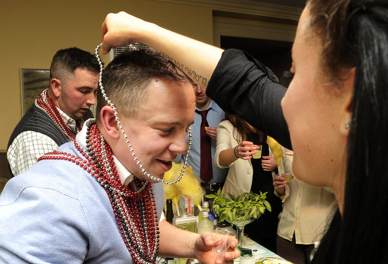 Adrian Trudeau, a bartender at Academe in Kennebunk, receives a set of beads from a voter at Maine Restaurant Week's Signature Event at the Portland Harbor Hotel Wednesday evening. His cocktail contained basil and cucumber vodka.