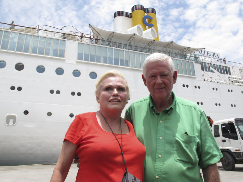 Costa Allegra passengers Gordon Bradwell and his wife, Eleanor, of Athens, Ga., pose in front of the cruise ship in Victoria's harbor, Seychelles Islands, Thursday.